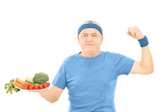 Mature man holding plate full of vegetables and showing strength. Isolated on white background royalty free stock image