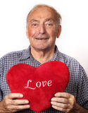 Mature man holding a red heart Stock Images