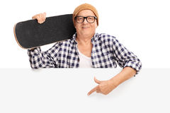 Mature man holding a skateboard behind a panel. Mature man holding a skateboard behind a blank panel and pointing on the panel with his finger isolated on white Stock Photos