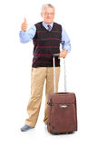 Mature man holding a suitcase and giving thumb up Royalty Free Stock Photo