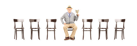 Mature man holding a trophy seated on wooden chair Royalty Free Stock Photography