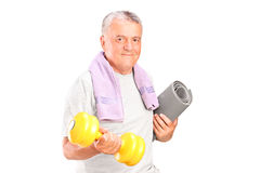 Mature man holding weight and mat Stock Photography