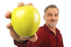 Mature man holds an apple. A smiling, mature man with a beard holds out an apple for all to see stock images