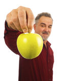 Mature man holds an apple by its stem Stock Photo