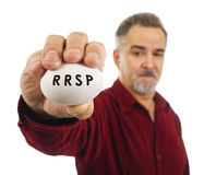Mature man holds an egg with RRSP on it. Stock Images