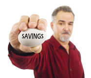 Mature man holds an egg with 'Savings' on it. stock images