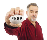 Mature man holds a white nest egg with RRSP on it stock image