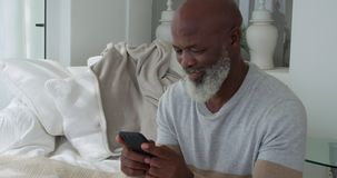 Mature man at home. Front view close up of a mature mixed race man using a smartphone at home stock video footage