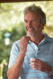 Mature Man At Home Taking Tablet Royalty Free Stock Photos