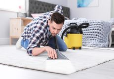 Mature man hoovering carpet with vacuum cleaner royalty free stock photography