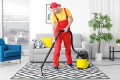 Mature man hoovering carpet with vacuum cleaner stock photo