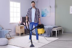 Mature man hoovering carpet with vacuum cleaner. At home stock images