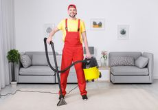 Mature man hoovering carpet with vacuum cleaner stock photography
