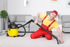Mature man hoovering carpet with vacuum cleaner stock images