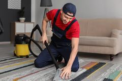 Mature man hoovering carpet with vacuum cleaner stock image