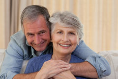 Mature man hugging his wife. Looking at the camera stock images