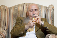 Mature man igniting cigar while sitting on armchair Royalty Free Stock Photography