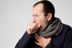 Mature man is ill from colds or pneumonia. Mature man in scarf is ill from colds or pneumonia. Suffering from flu virus Royalty Free Stock Images
