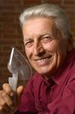 Mature man with inhalator. Mature man in a shirt with inhalator royalty free stock images