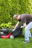 Mature man installing grass bag on old lawnmower Stock Photos