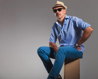 Mature man in jeans wearing hat and sunglasses while seated Royalty Free Stock Photo