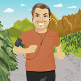 Mature man jogging in mountains with smartphone armband listening to music playlist on mobile phone app. Mature man jogging in the mountains with smartphone Royalty Free Stock Photos