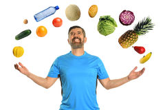Mature Man Juggling Food. Mature Hispanic man jugglung fruits adn vegetables isolated over white background stock photo