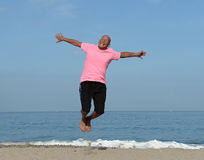 Mature man jumping on beach. Mature man jumping on sandy beach on sunny day royalty free stock photo
