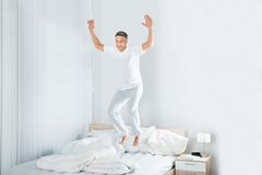 Mature man jumping on bed. Happy Excited Mature Man Jumping On Bed At Home Royalty Free Stock Photo