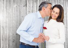 Mature man kissing while giving a red rose to woman Stock Photography