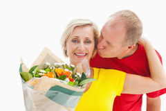 Mature man kissing his partner holding flowers Stock Photos