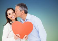 Mature man kissing woman holding a heart Stock Images