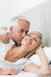 Mature man kissing womans cheek in bed Royalty Free Stock Photos