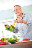 Mature man in the kitchen prepare salad. Modern ambience Royalty Free Stock Images