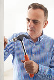 Mature Man Knocking Nail Into Wall With Hammer Stock Images