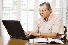 Mature man with laptop. royalty free stock image