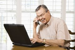 Mature man with laptop. Mature Caucasian man typing on laptop and talking on cellphone royalty free stock photos