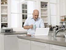 Mature Man With Laptop And Coffee Cup In Kitchen Royalty Free Stock Images