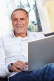 Mature man with laptop Stock Photos