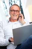 Mature man with laptop, mobilephone and reading specs Stock Photo