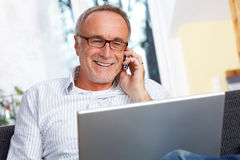 Mature man with laptop mobilephone and reading specs. Sitting at home Stock Photography
