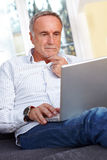 Mature man with laptop, thinking Stock Photos