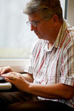 Mature man on laptop on train Stock Photo