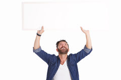 Mature man laughing and holding blank poster sign. Portrait of mature man laughing and holding blank poster sign on white background royalty free stock image