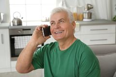 Mature man laughing while talking on phone. At home royalty free stock images