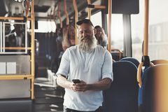 Mature man laughing at a text message on the bus. Smiling mature men with a long beard reading text messages on his cellphone while standing on a bus during his royalty free stock images