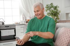 Mature man laughing while using smartphone. At home stock images