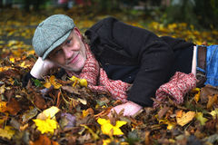 Mature man laying in a pile of autumn leaves. Royalty Free Stock Photo