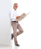Mature man leaning against a wall and reading newspaper Royalty Free Stock Images