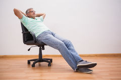 Mature man leaning back in swivel chair Stock Photos